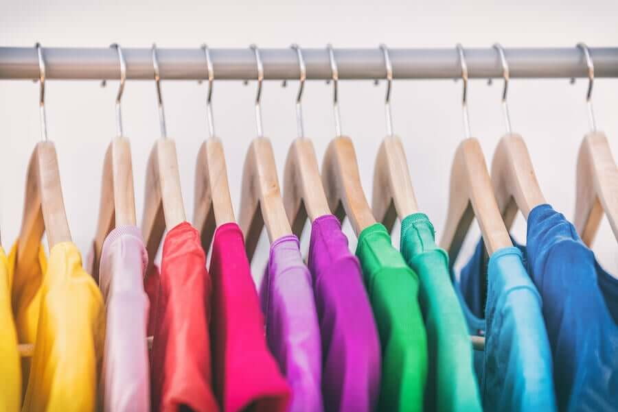 A row of brightly colored shirts on hangers.