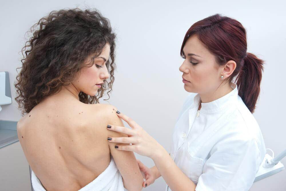 doctor looking at a woman's mole