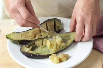 Someone scooping out eggplants.