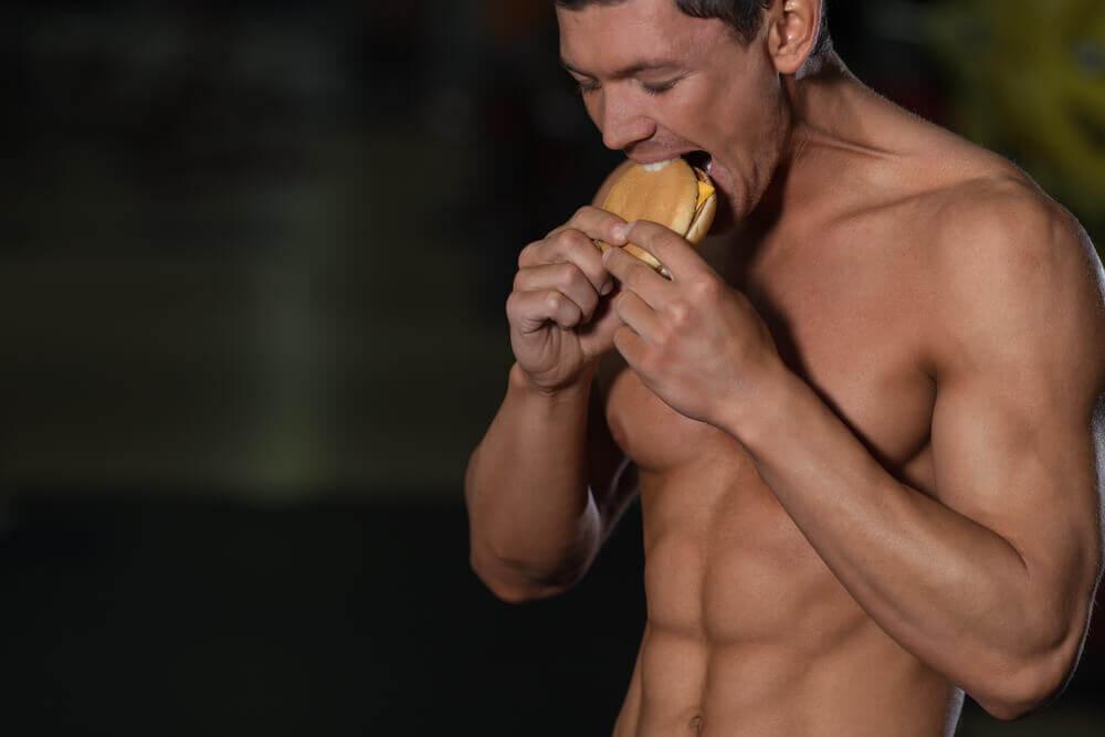 A man eating a hamburger and exercising.