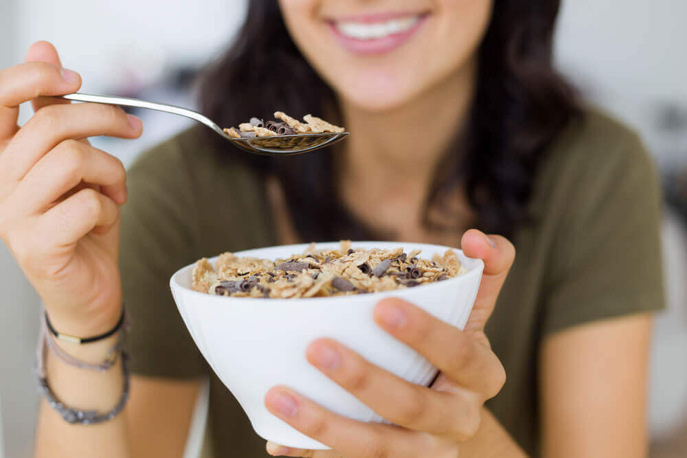 A woman eating a bowl of granola
