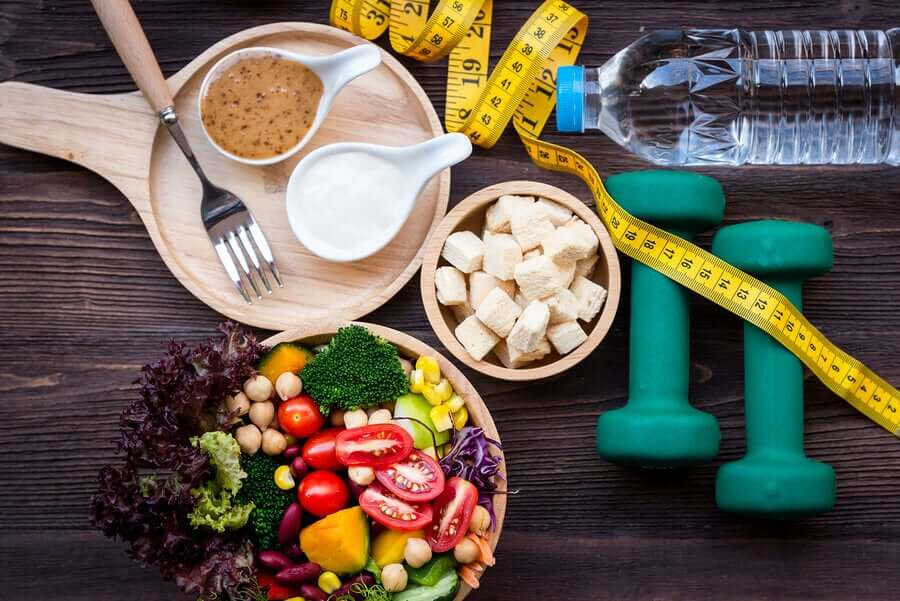 A healthy salad, a measuring tape, a bottle of water, and dumbells.