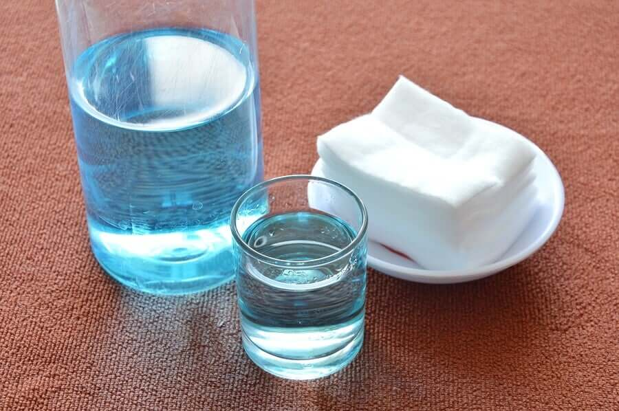 Two cups of blue liquid next to a pile of cotton pads.