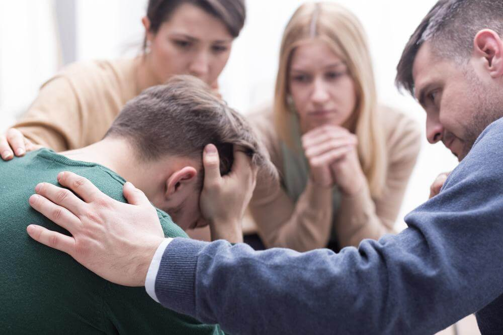 a group of friends consoling a man