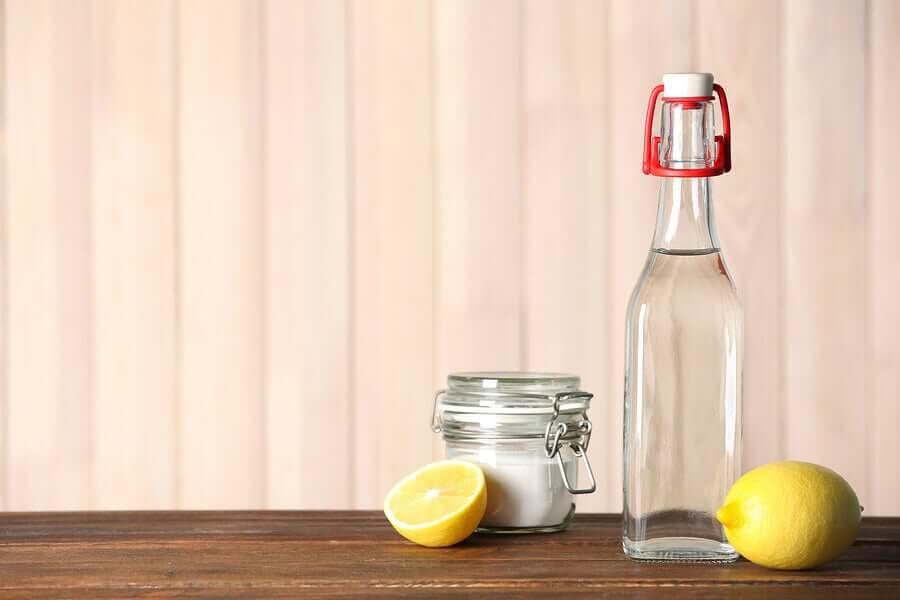 A bottle of vinegar, a jar of baking soda, and lemons.