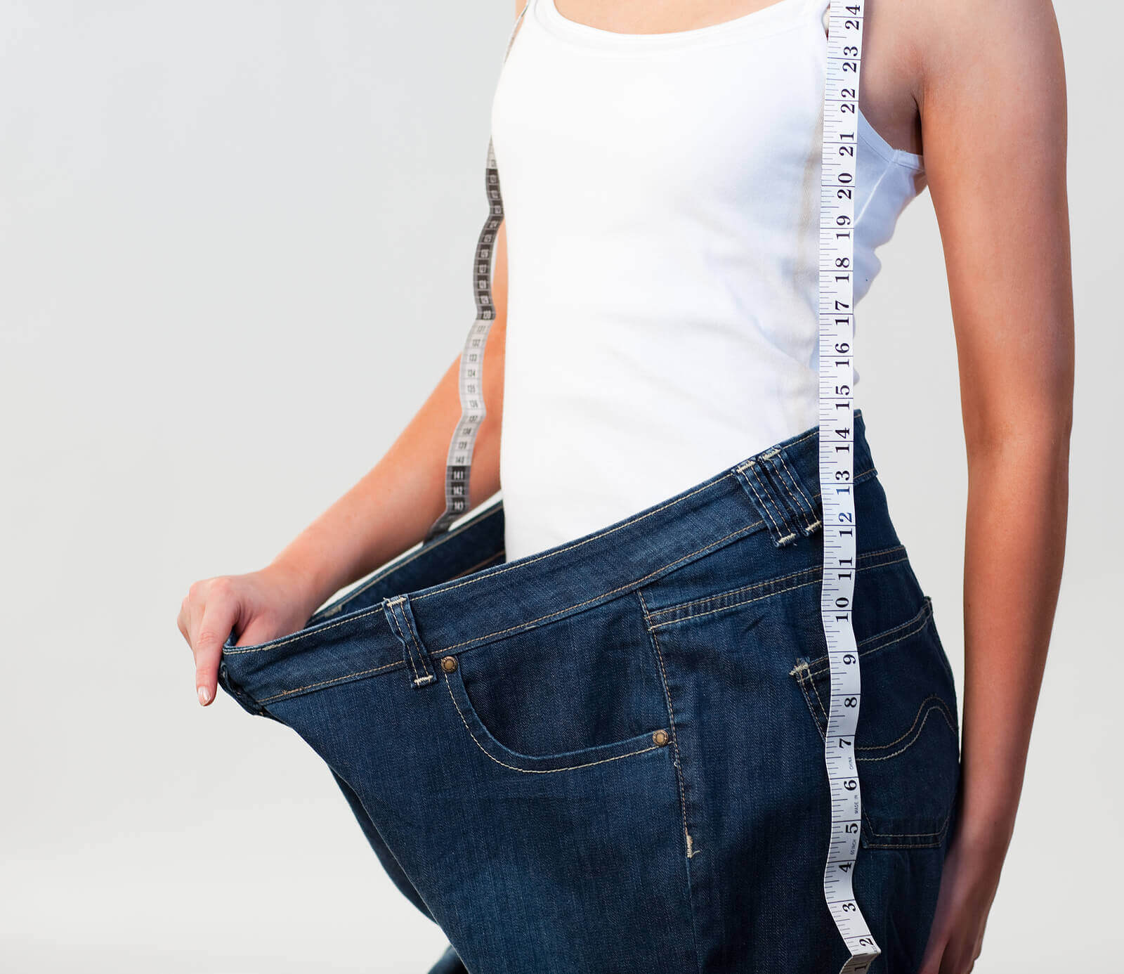 A thin woman standing in a large pair of jeans.
