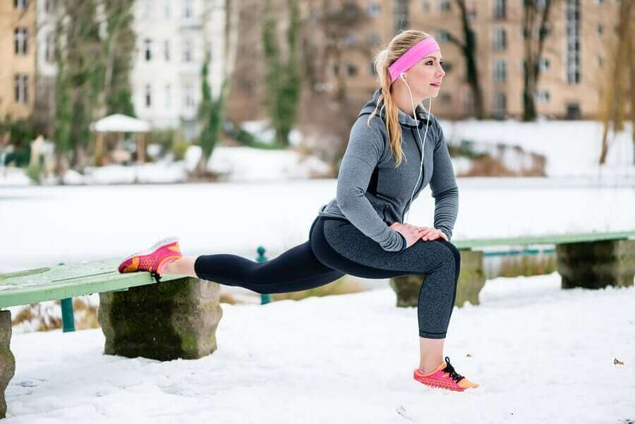 A woman stretching for a run in the winter.