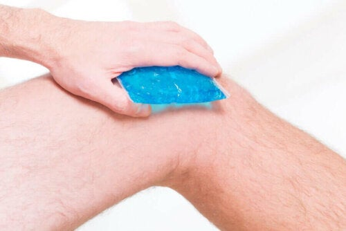 A person putting an ice pack on their knees.