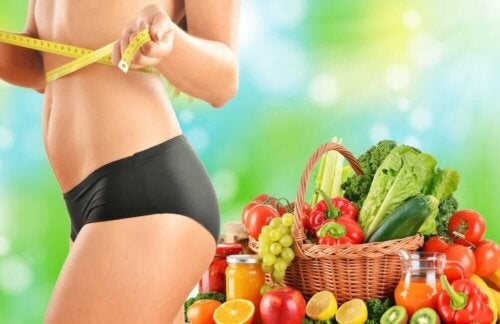 A woman measuring her waist beside some fruit and vegetables.