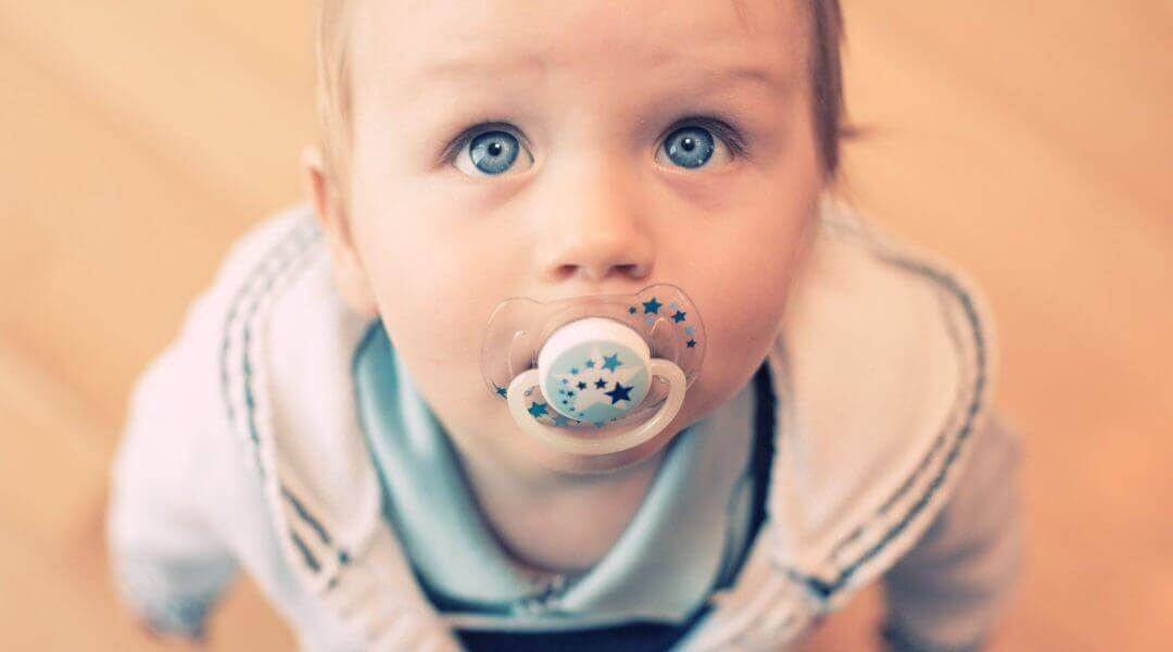 Child with pacifier looking up at photographer