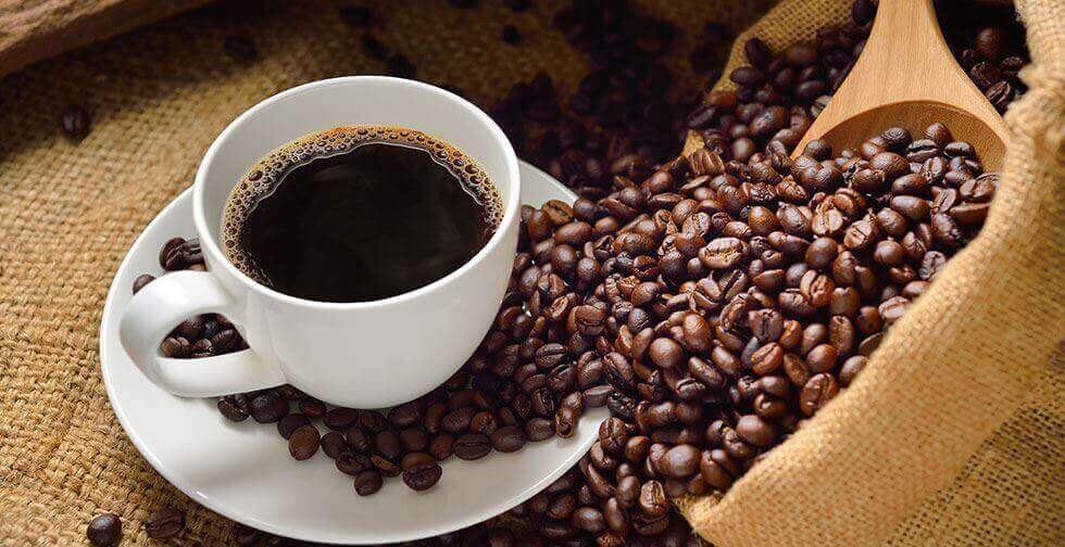 A cup of coffee with some beans