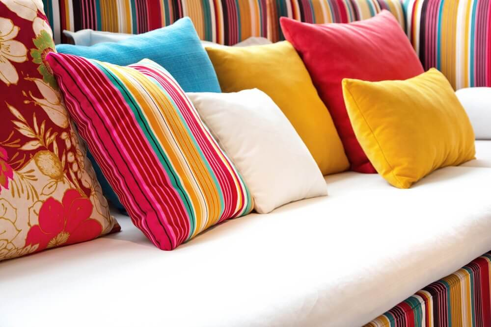 A sofa covered in decorative cushions