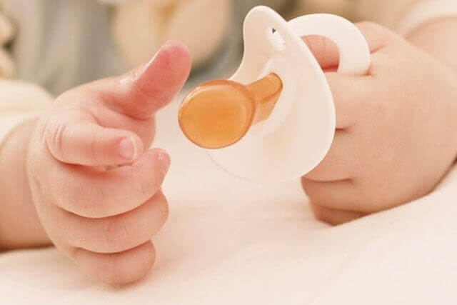 Close up of baby's hands holding a pacifier