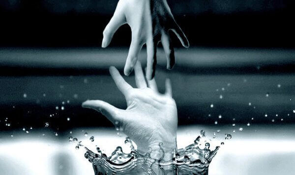 Two hands reaching for each other out of the water