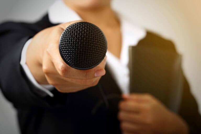 A woman extending a microphone