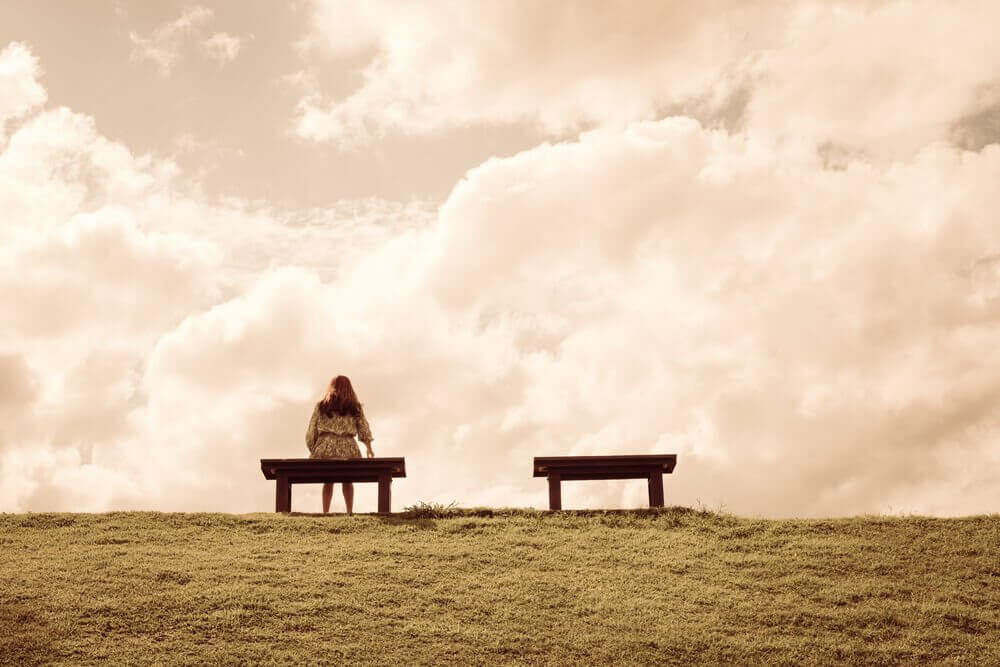 A woman sitting alone on a bench on a hill.