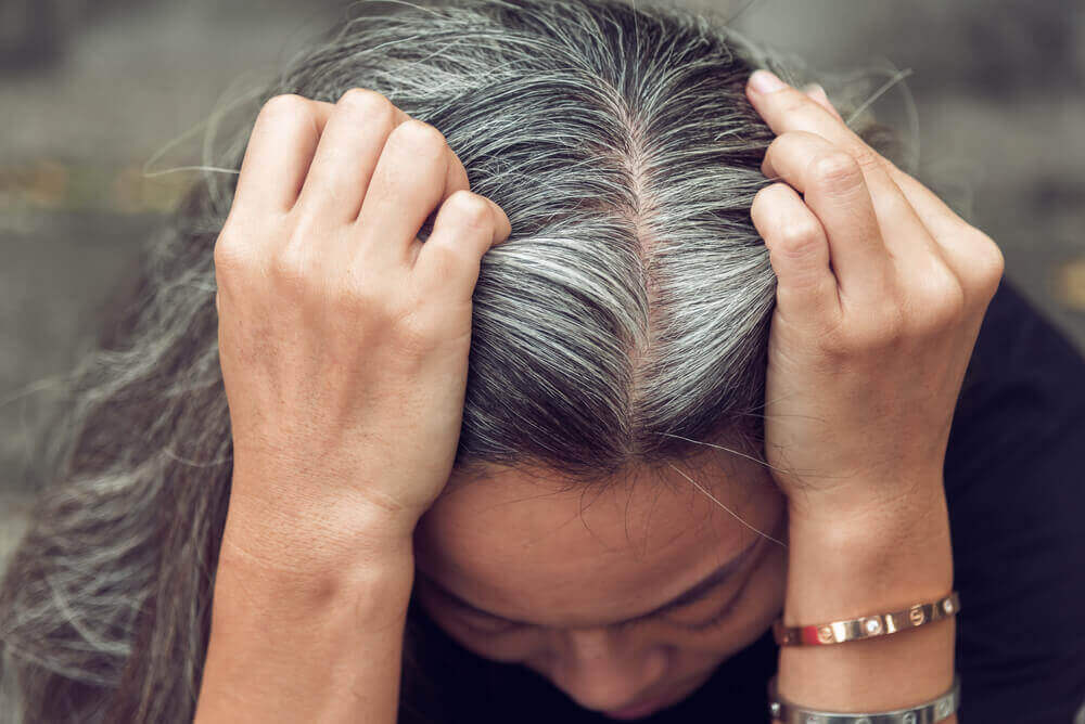 A woman showing her grey hair.