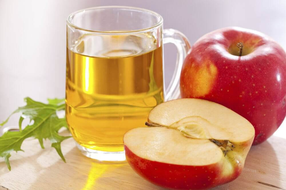 A glass of apple juice next to an apple