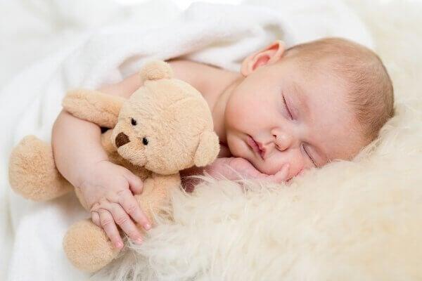 A sleeping baby with a teddy bear.
