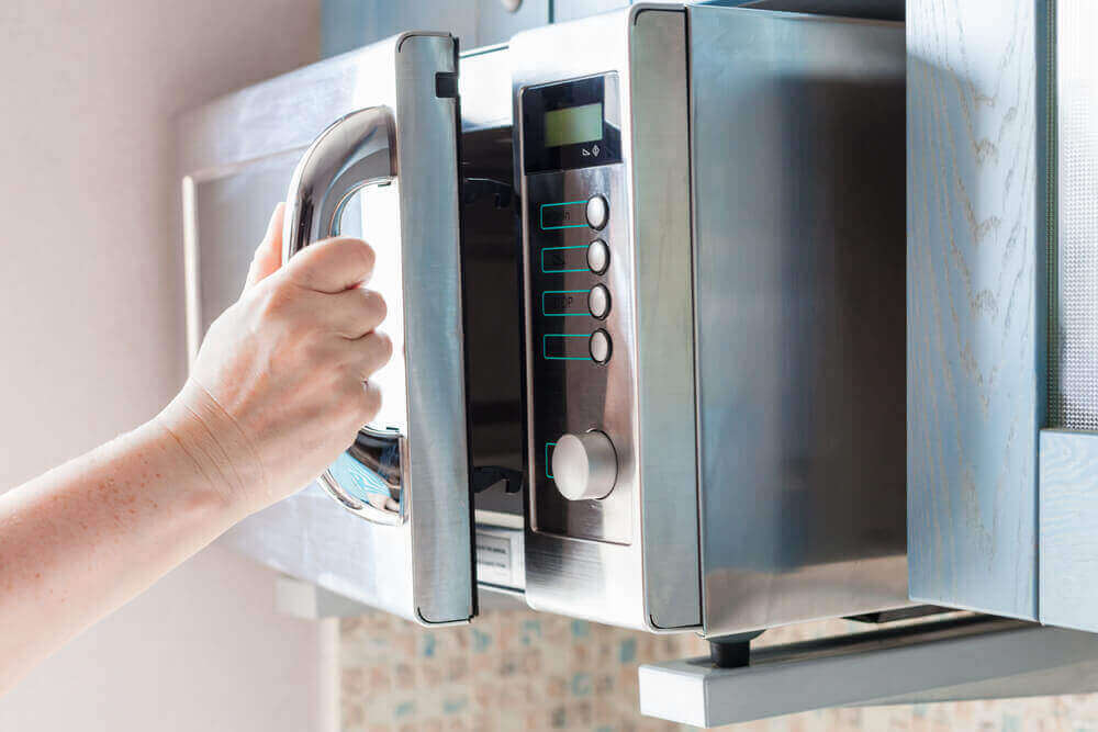 A hand opening a clean microwave.