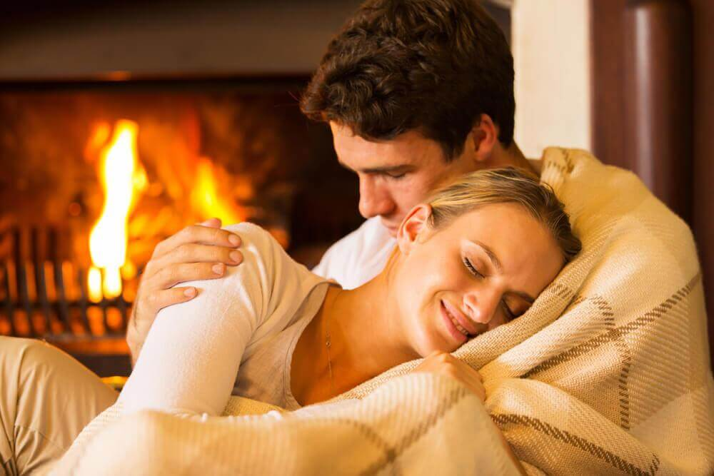 couple warming up in front of a fireplace