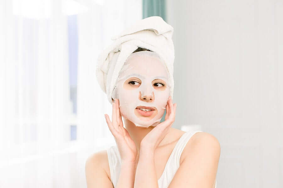 A woman applying a face mask.