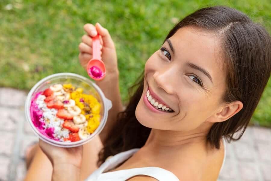 A girl eating a fruit salad.