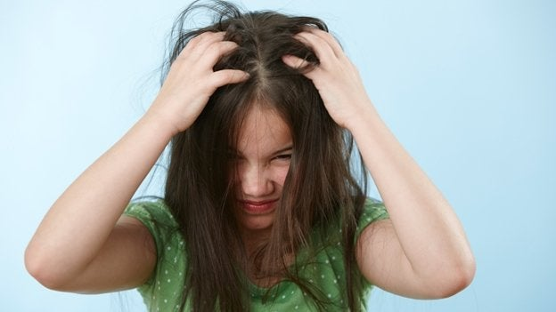 A girl itching her head because she has head lice