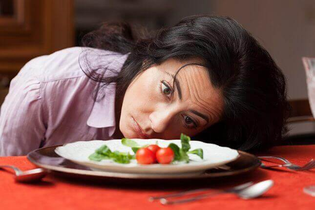 A hungry woman staring at a plate of food.