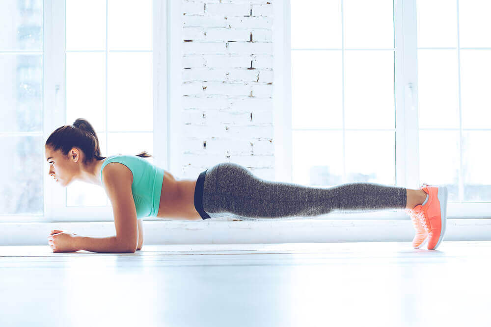 A side view of a woman doing the plank.