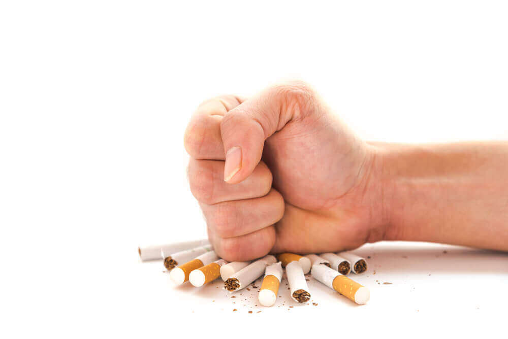 A hand smashing a pile of cigarettes.