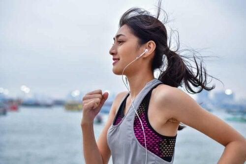 woman running with headphones in enjoying herself smiling