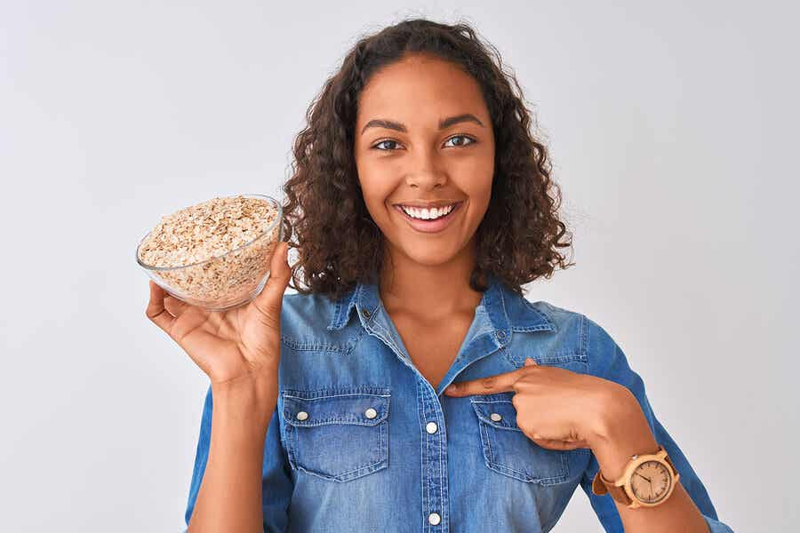 woman smiling holding up a bowl of oats and pointing to it