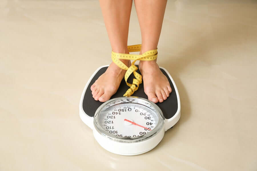 A woman standing on a weighing scale.