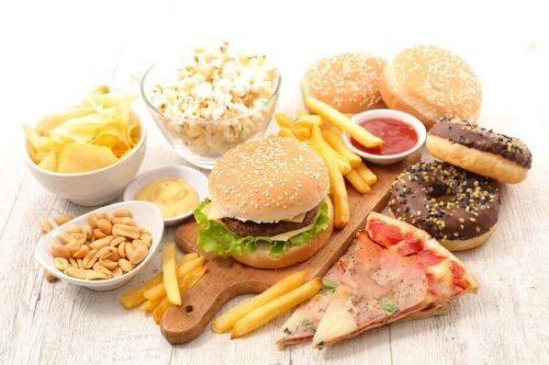A bunch of junk food on a wooden table.