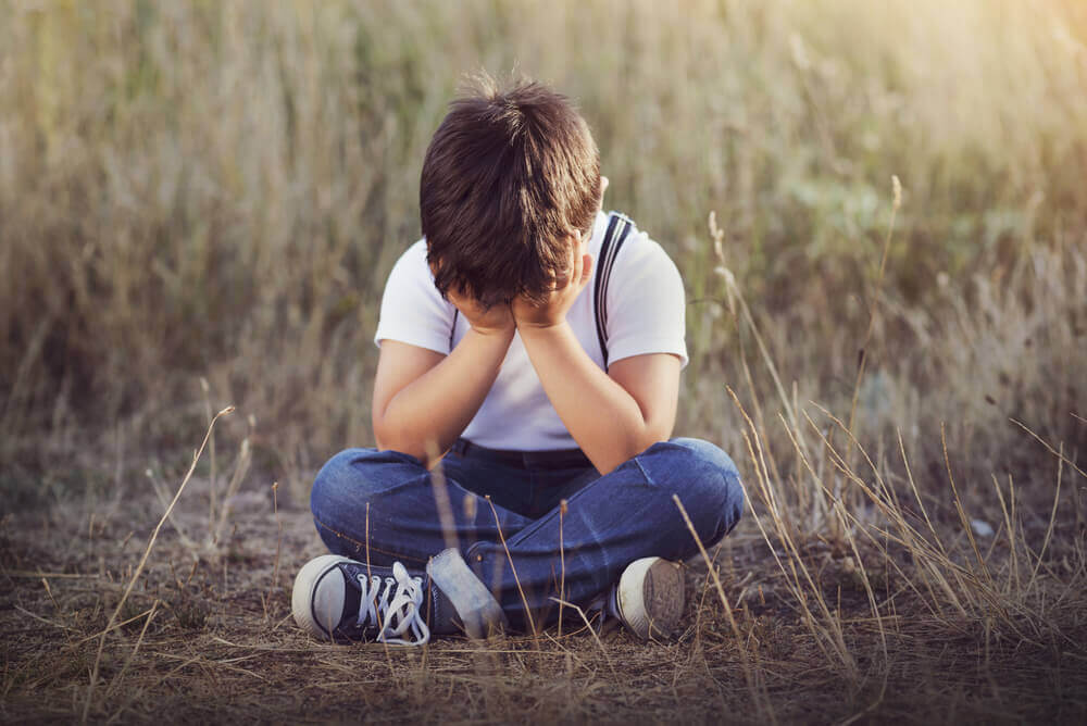 Child sitting crying in a field because their parents didn't tell them what to do if they get lost