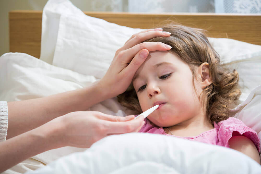 Child in bed having temperature taken, dry cough in children