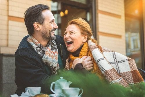 Older couple laughing together outside a café