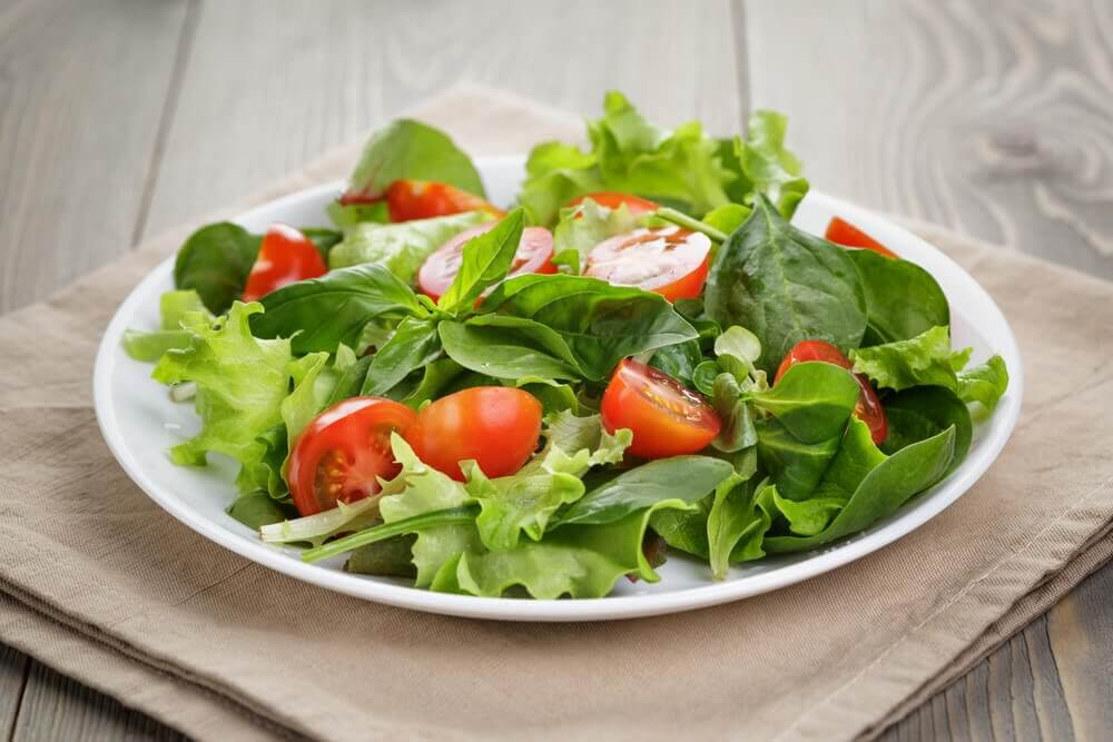 Tomato salad on a small plate because using smaller plates is one of the mental tricks to help lose weight