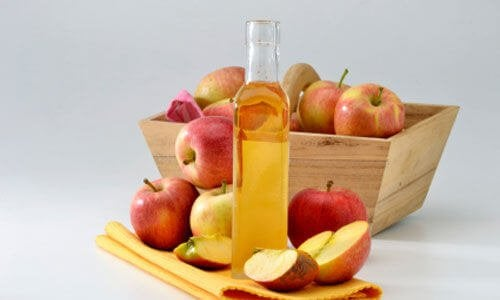 A bottle of apple cider vinegar with some apples