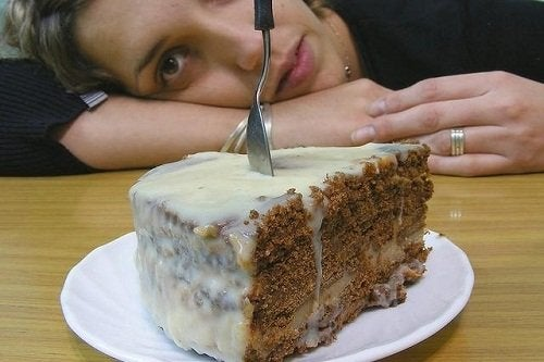A woman with a sweet craving looking at cake.