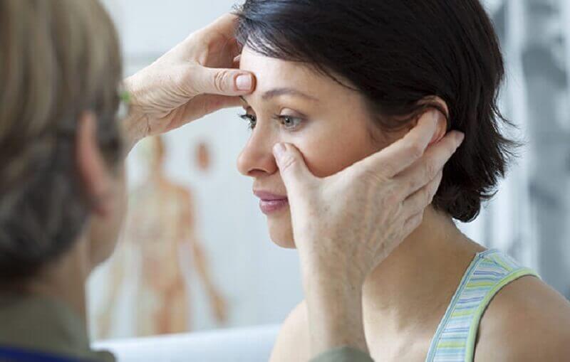 A doctor examining a woman for nasal polyps.