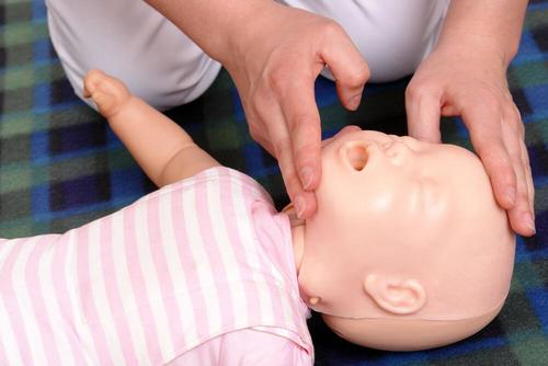 A person tilting a baby's head back to resuscitate