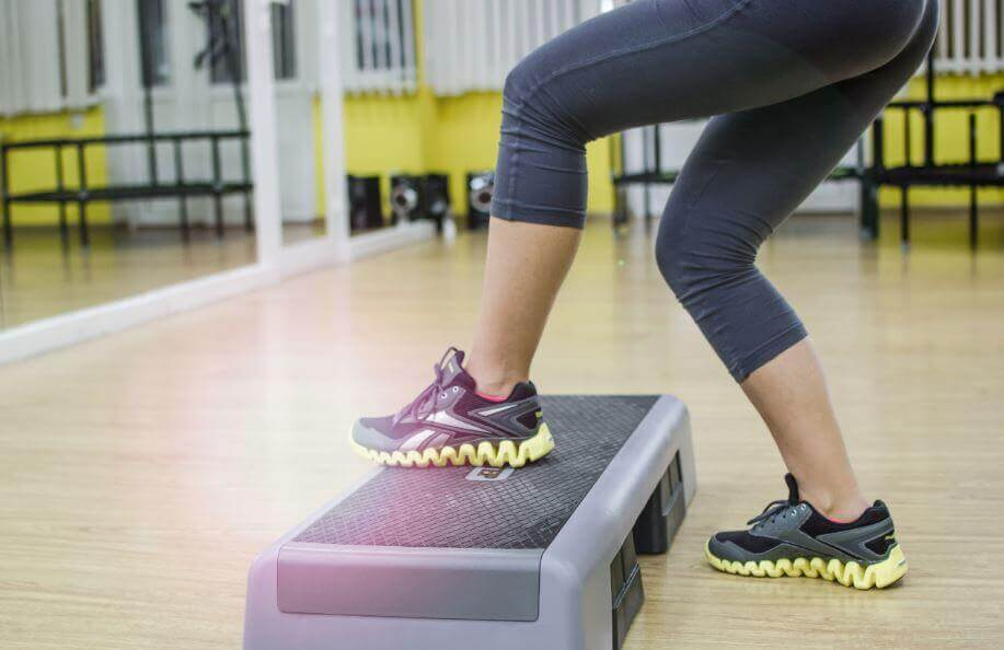 A woman doing steps in a gym.