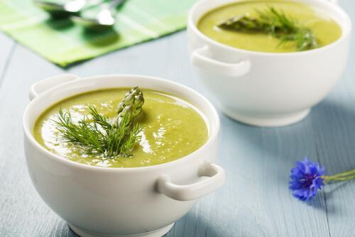 Two bowls of cream of asparagus soup.