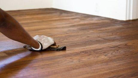 A woman cleaning her hardwood floors.