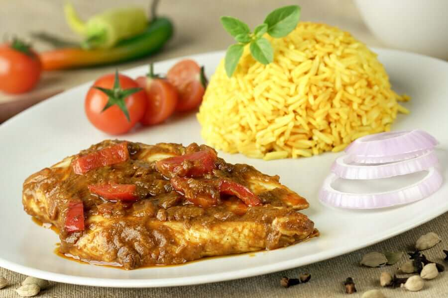 A plate with chicken, rice, tomatos, and onions.