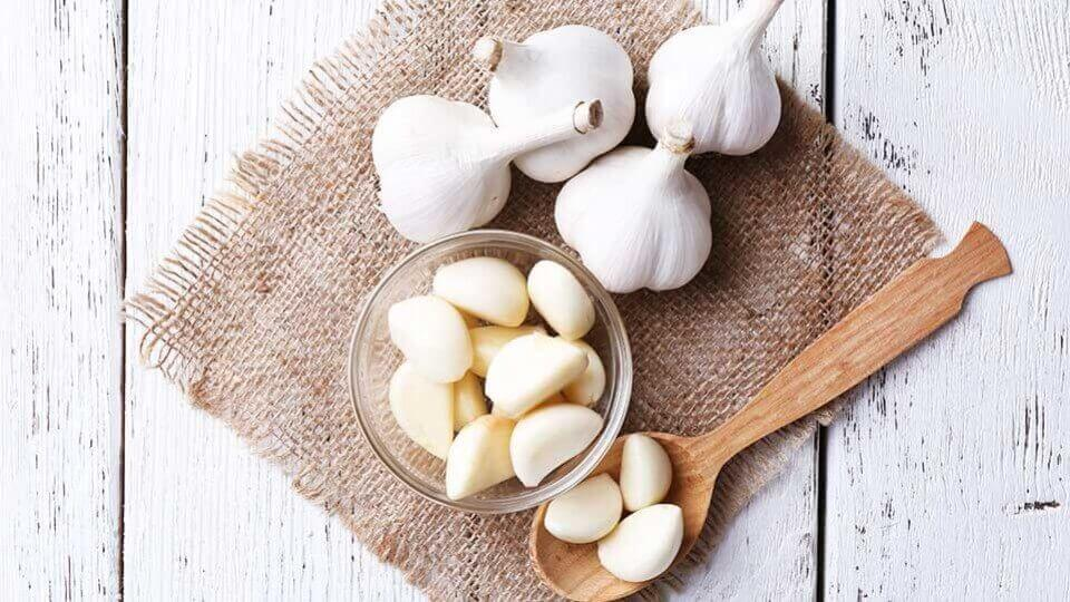 Four heads of garlic and a bowl of peeled garlic cloves.