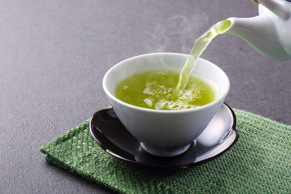 Pouring a cup of green tea.