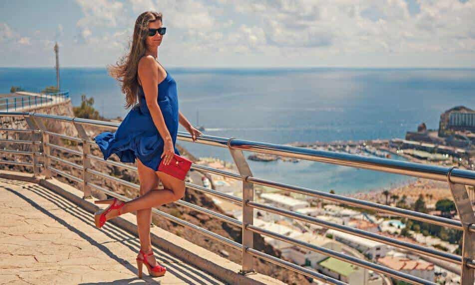 A woman looking over the ocean with heels.